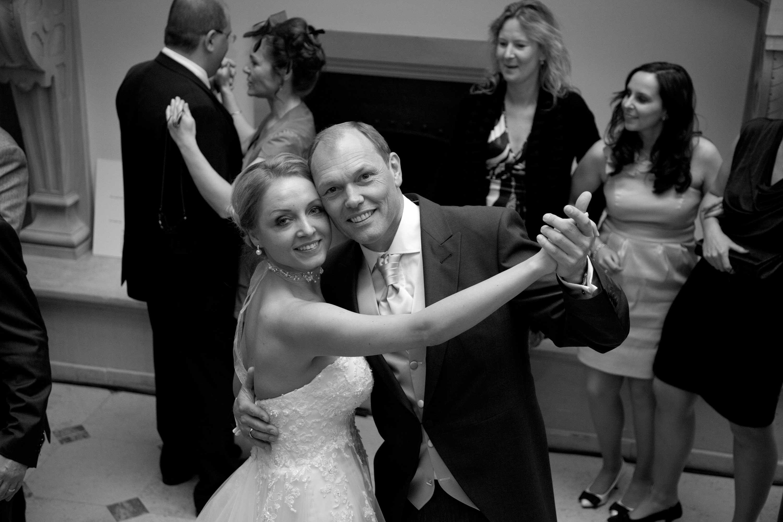 Hochzeitstanz. Im Hintergrund tanzen die Gäste. Schwarz-weiß-Foto.
