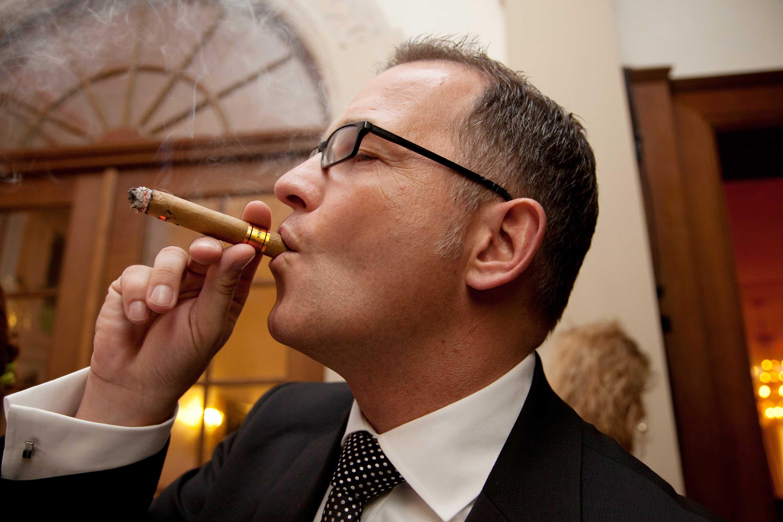 Der Trauzeuge raucht eine Zigarre während der Hochzeitsfeier.