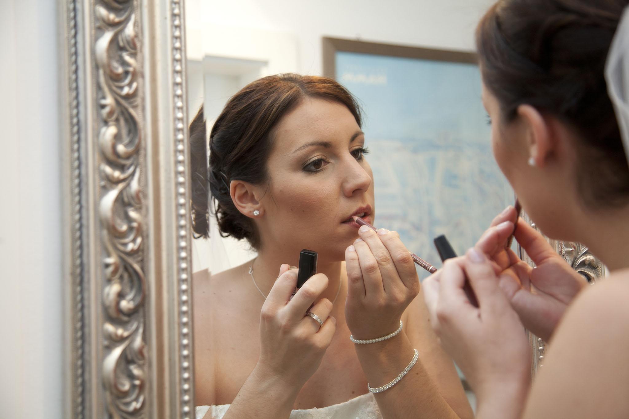Die Braut schminkt sich beim Dress Up am Hochzeitstag. Sie spiegelt sich und schminkt ihre Lippen. Sie hat ein Hochzeitskleid an und trägt Schmuck.