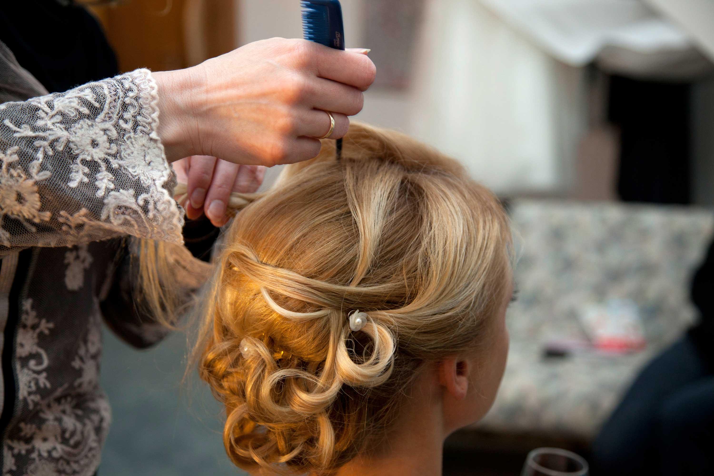 Hochsteckfrisur der Braut vor der Hochzeit. Die Friseurin arrangiert die blonden Haare mit einem Kamm hoch. Im Haar stecken weiße Perlen und Blumen.