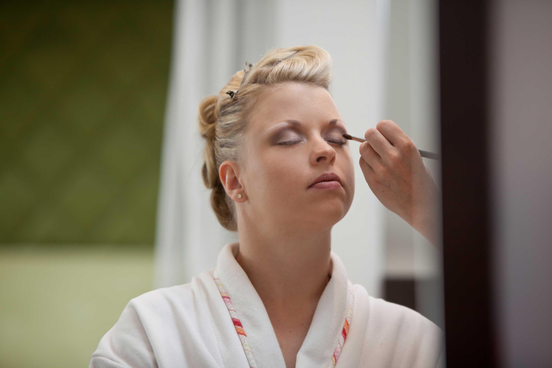 Die Braut wird im weißen Bademantel geschminkt. Sie hat die Augen geschlossen und mit einem Pinsel wird ihr der Lidschatten aufgetragen.