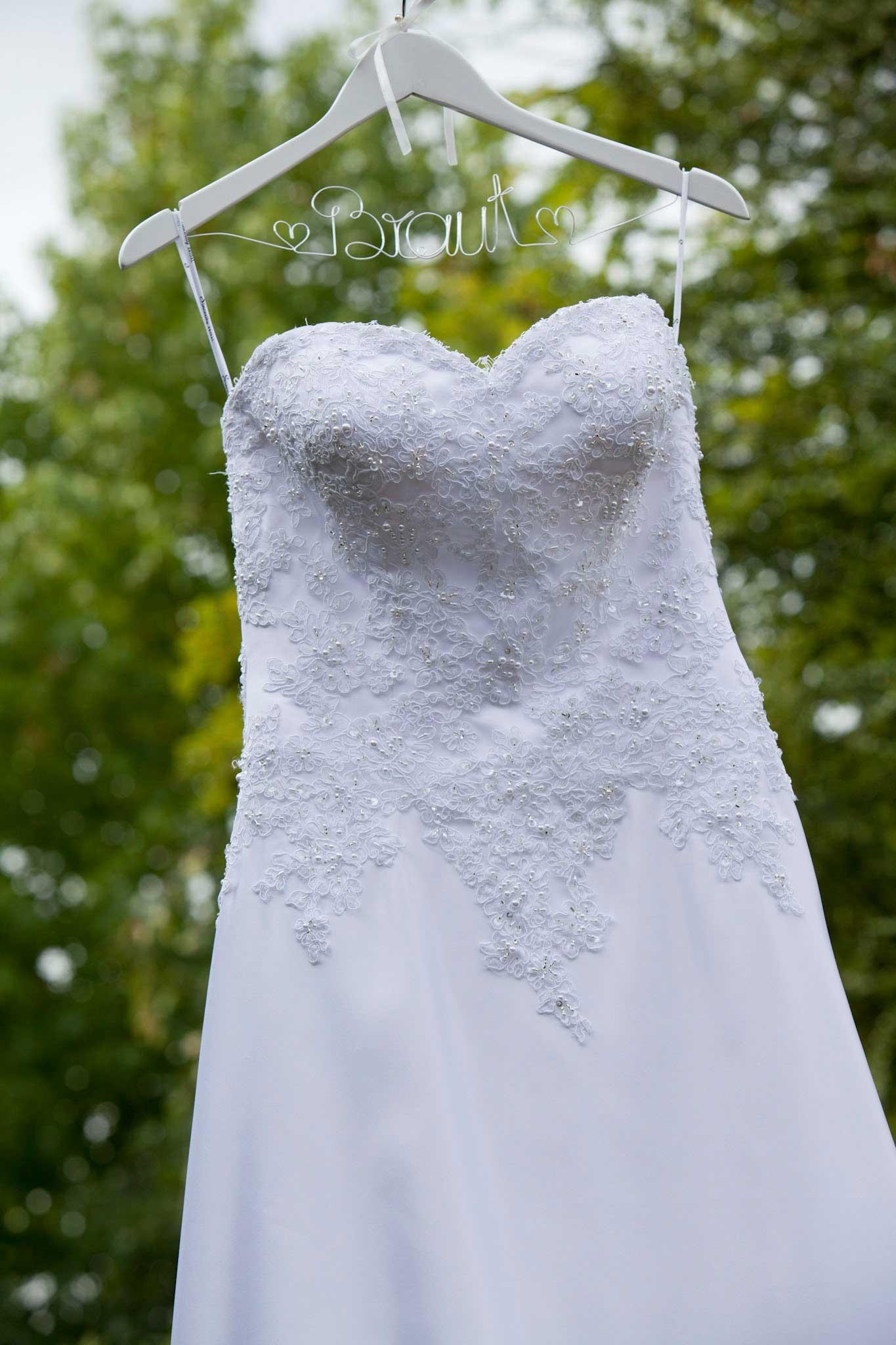 Ein weißes Brautkleid hängt an einem weißen Kleiderbügel. Der Kleiderbügel ist verziert mit einem silbernen Draht aus dem das Wort Braut geformt ist. Im Hintergrund sieht man grüne Bäume in der Unschärfe.