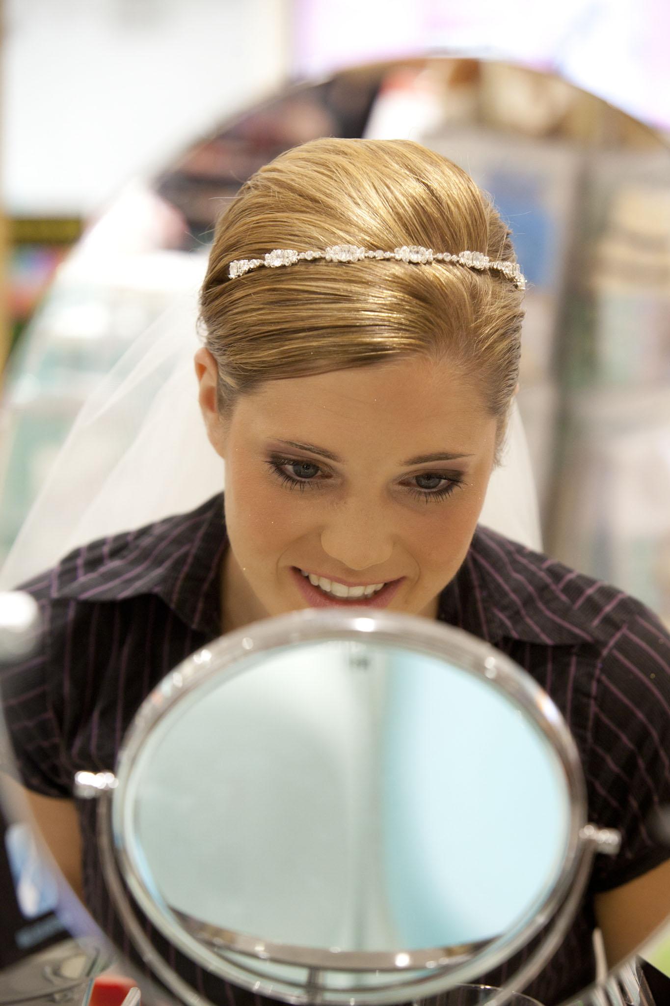 Die Braut sieht sich lächelnd im Spiegel an. Sie begutachtet ihr Make up. Sie trägt einen feinen Perlenhaarreif in der Hochzeitsfrisur.