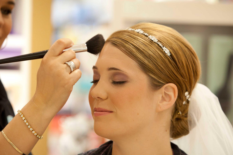 Die Braut wird geschminkt. Sie hat die Augen geschlossen. Mit einem großen, weichen Pinsel wird Puder aufgetragen. Sie hat einen feinen Perlenhaarreif in der Hochzeitsfrisur und trägt einen Schleier im Haar.