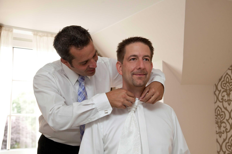 Der Trauzeuge hilft dem Bräutigam beim Anlegen der Krawatte.