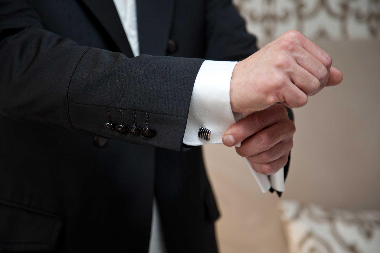 Der Bräutigam zieht sein Jacket an und richtet die Manchettenknöpfe am weißen Hemd.