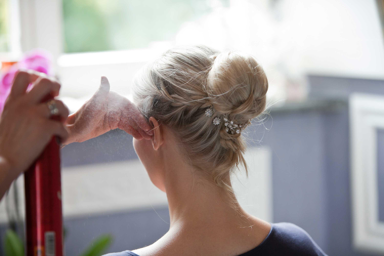 Die Brautfrisur ist fertig und wird mit Haarspray fixiert. Die blonden Haare sind mit einem geflochtenem Zopf und weißen perlen verziert.