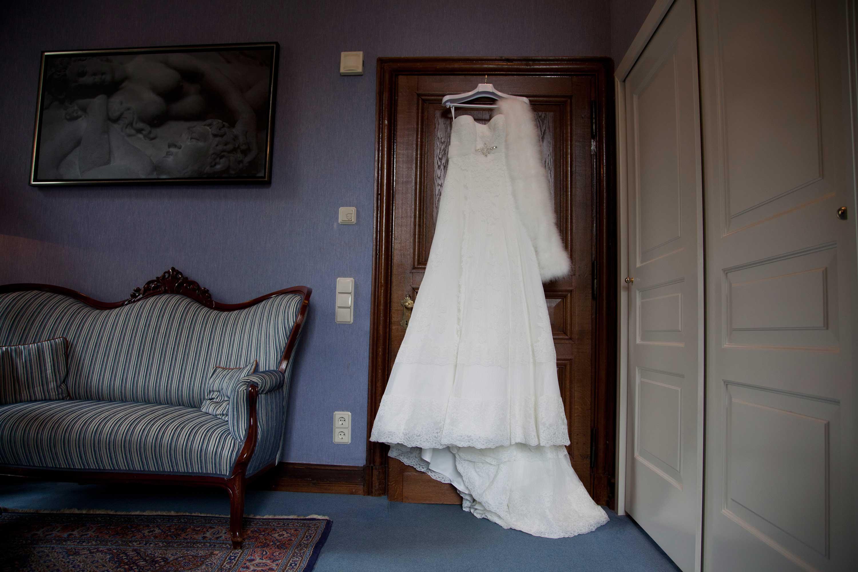 Das weiße, lange Brautkleid hängt an einer braunen Holztür an einem weißen Kleiderbügel. Im Raum steht ein Sofa
