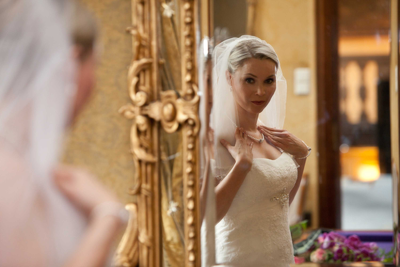 Die Braut sieht sich im goldenen Spiegel an. Sie trägt ein weißes Hochzeitskleid und einen Schleier. Ihre Hände berühren eine Perlenkette an ihrem Dekolleté.