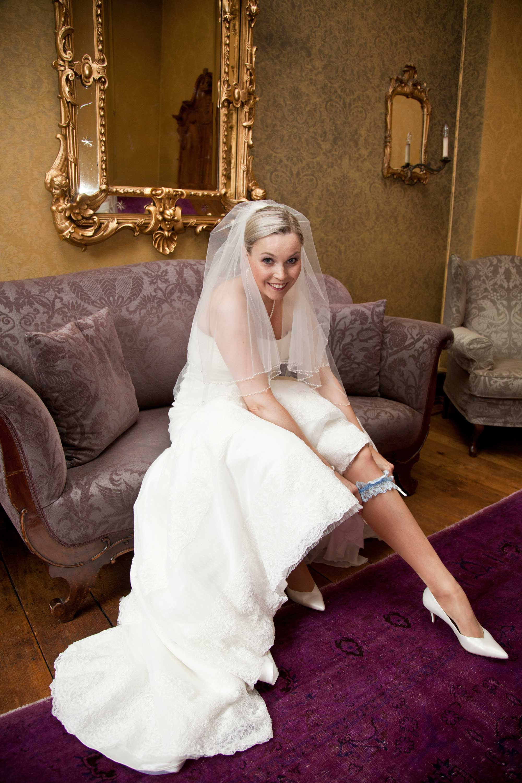 Die Braut zieht ihr Strumpfband an. Sie sitzt auf einem Sofa. Hinter ihr ist ein goldener Spiegel an der Wand und am Boden liegt ein pinkfarbener Teppich. Die Braut trägt einen Schleier und weiße Damenschuhe mit Absatz.