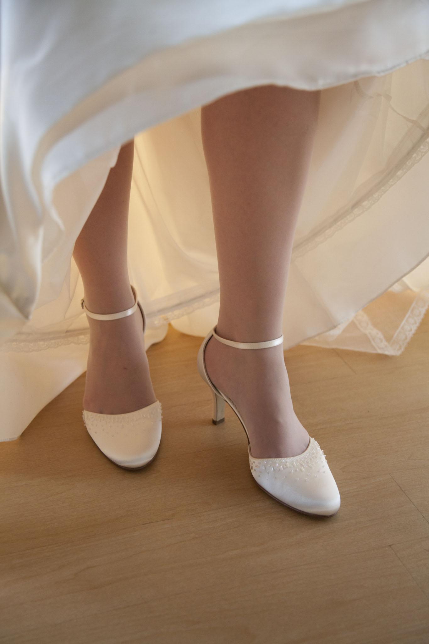 Weiße Damenschuhe mit Absatz unter dem Brautkleid.