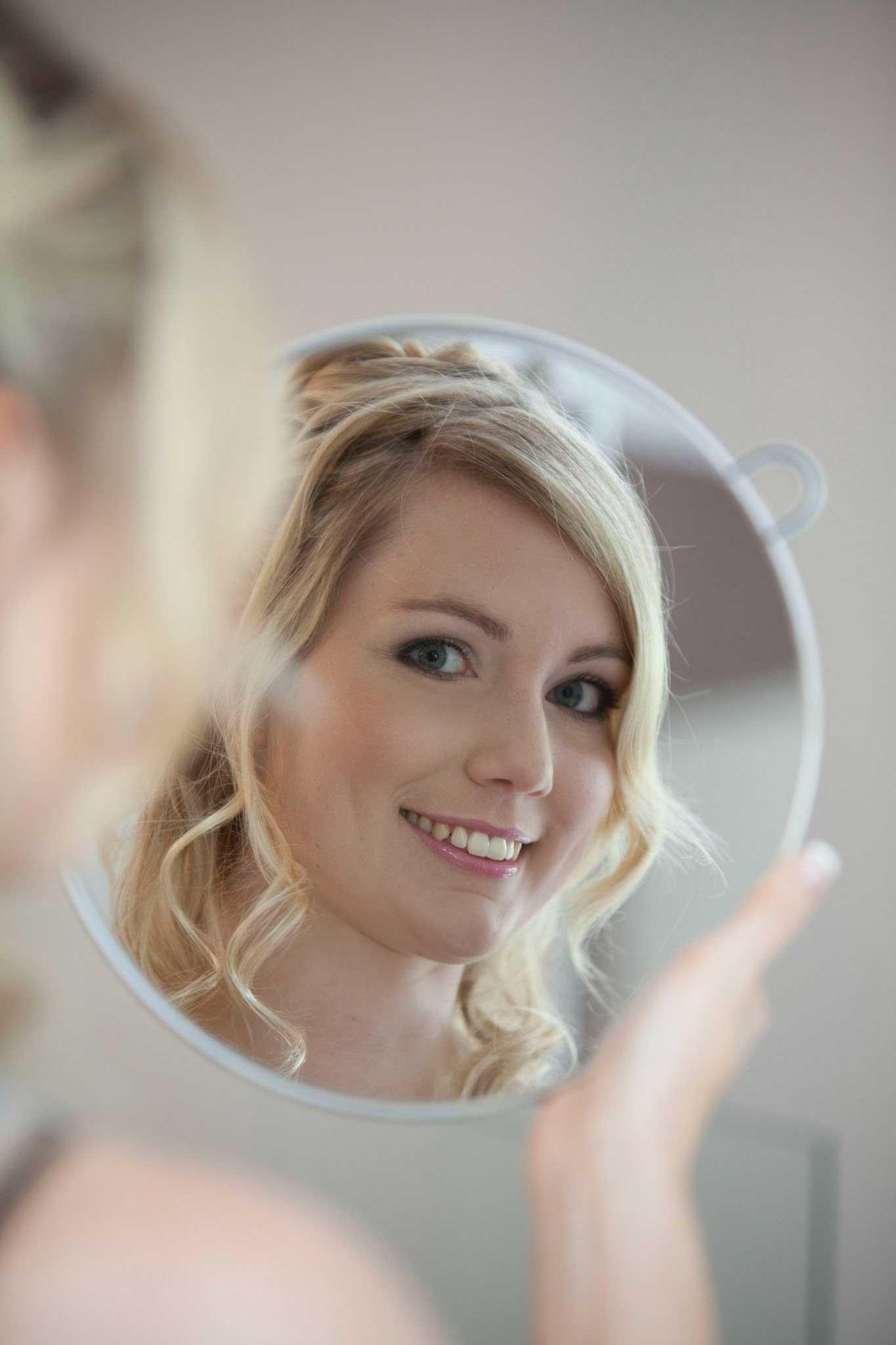 Die Braut sieht sich in einem runden Spiegel an.