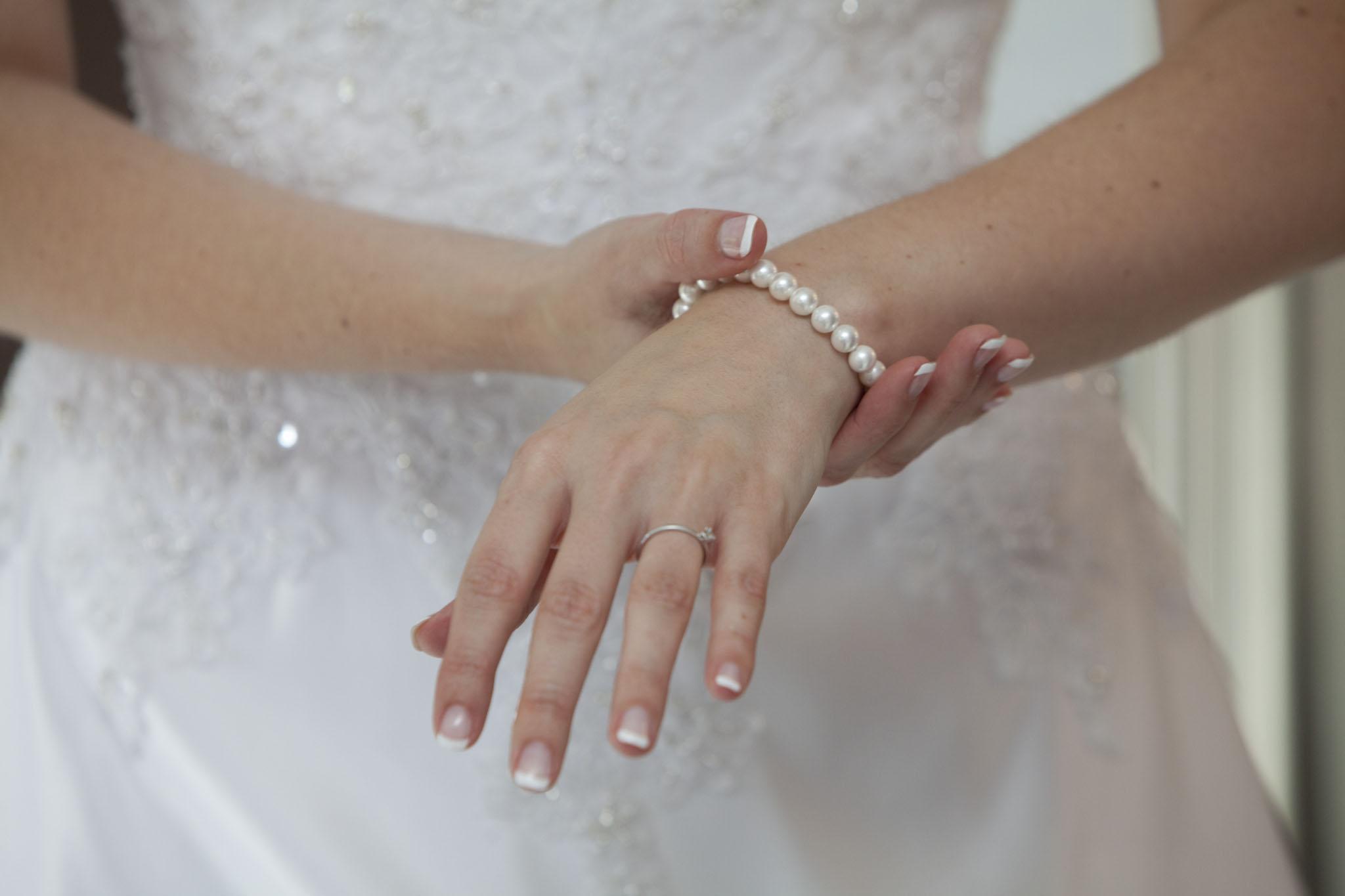Die Braut legt ihr Perlenarmband an.