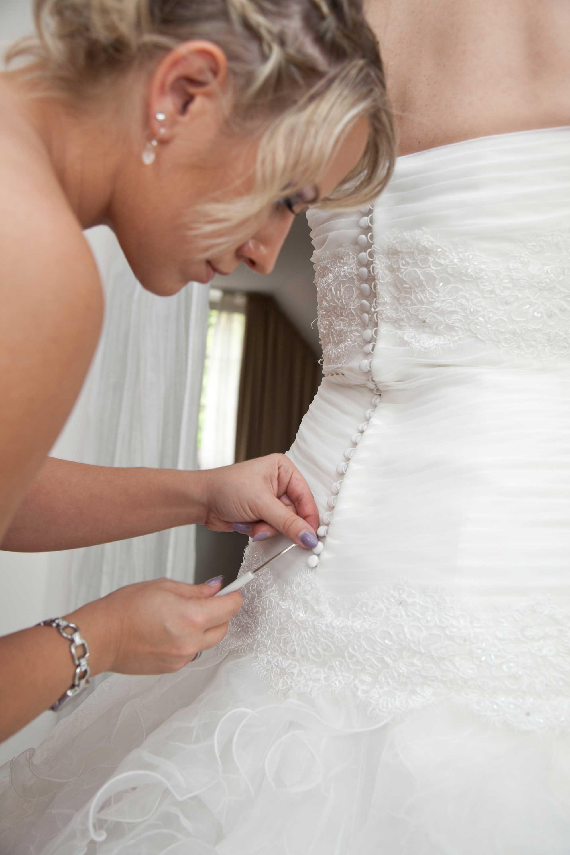 Die Brautzeugin knöpft das Brautkleid zu.