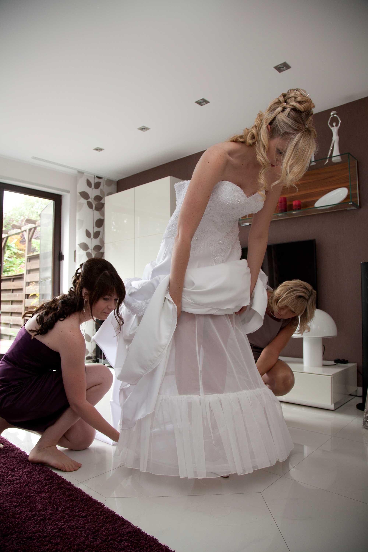 Die Braut zieht ihr Brautkleid an. Die Trauzeuginnen helfen ihr dabei. Sie richten den Unterrock.
