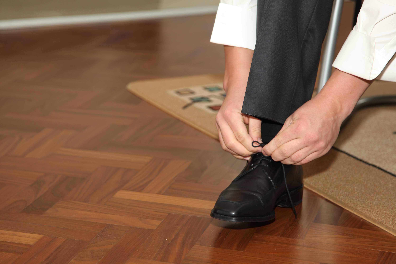 Der Bräutigam schnürt seine schwarzen Schuhe.