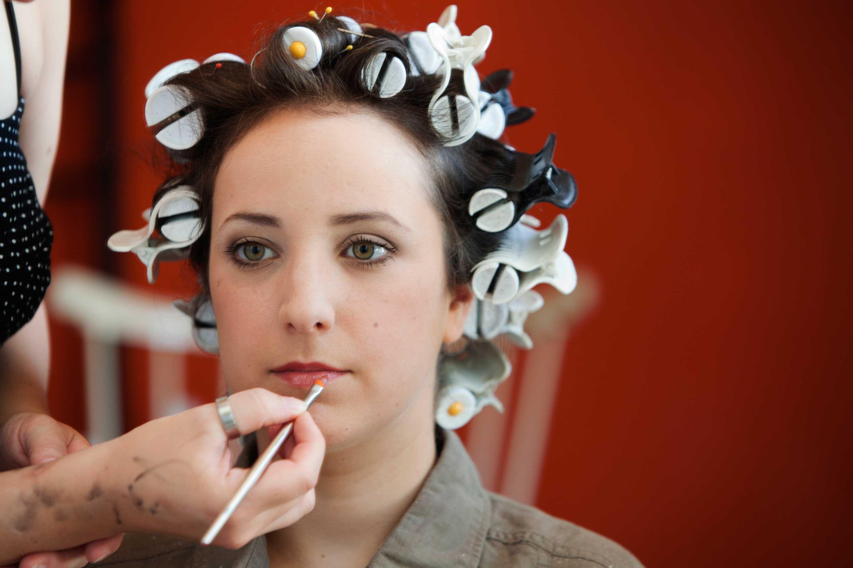 Die Braut wird geschminkt. Der Lippenstift wird aufgetragen. Sie hat Lockenwickler im Haar. Hinter ihr ist eine rote Wand.