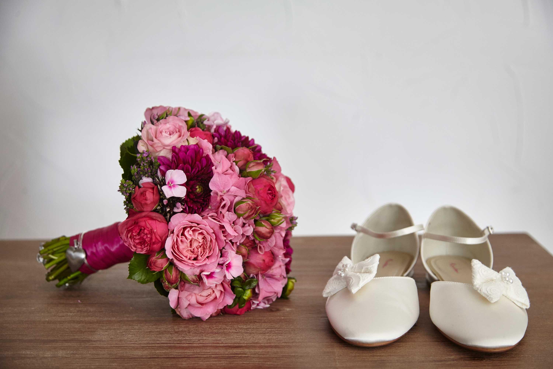 Ein Stilleben mit einem Brautstrauß und weißen Brautschuhen. Der Strauß hat rosa und pinkfarbene Blumen und ist mit einem kleinen silbernen Herz verziert.