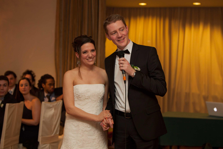 Das Brautpaar bei einer gemeinsamen Hochzeitsrede. Sie stehen neben einander und halten sich an den Händen. Der Bräutigam hält das Mikrophon in der Hand. Im Hintergrund sind die Hochzeitsgäste.