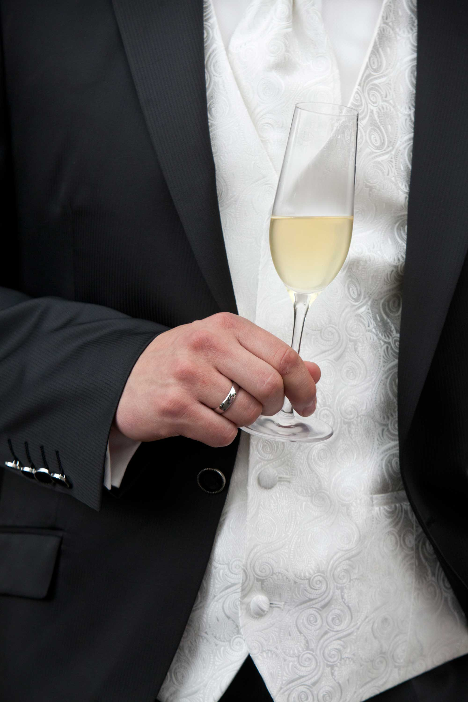 Der Bräutigam hält ein Sektglas in der Hand. Er trägt seinen Ehering.