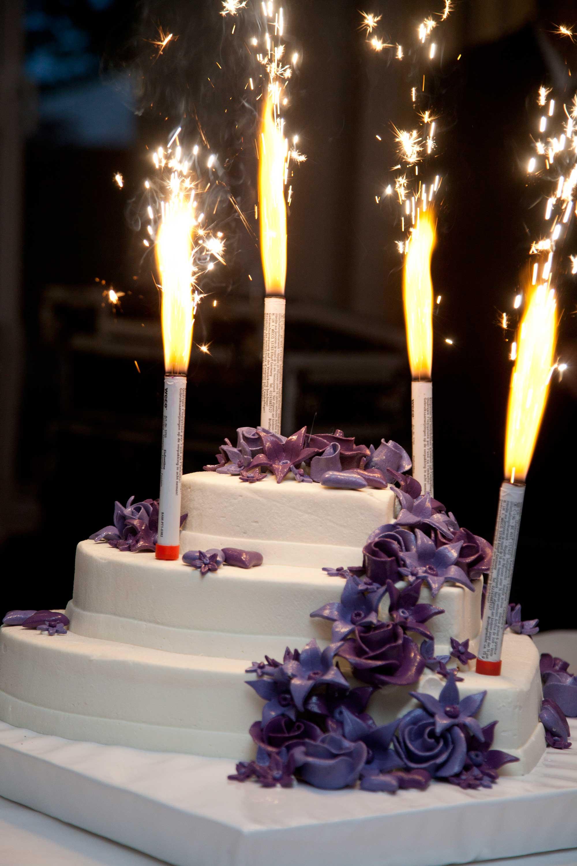 Die Hochzeitstorte mit Feuerwerk. Funken sprühen. Die Torte ist verziert mit lila Zuckerblumen.
