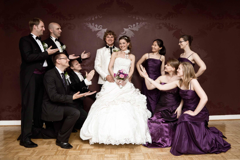 Das Hochzeitspaar mit den Trauzeugen und Freunden. Gruppenfoto vor einer Tapete mit Ornamenten. Links vom Paar sind die Männer und rechts die Frauen. Sie zeigen auf das Brautpaar.