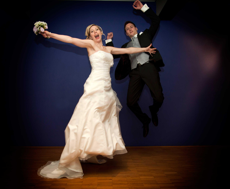 Das Brautpaar springt in die Luft während der Hochzeitsfeier.