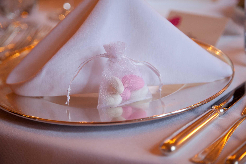 Tischdekoration bei der Hochzeitsfeier. Kleines, weißes Säckchen mit Süßigkeiten auf einem silbernen Teller. Dahinter ist eine weiße Serviette.