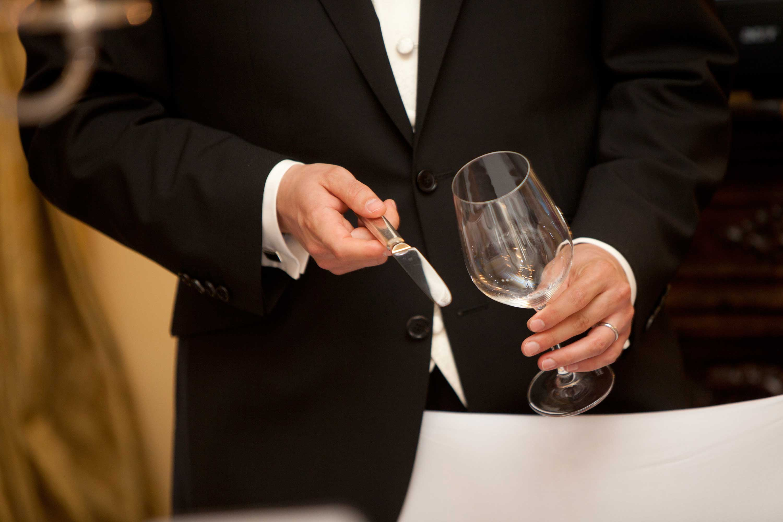 Der Bräutigam klopft mit einem Messer an ein leeres Glas um die Aufmerksamkeit zu erlangen. Detailaufnahme.