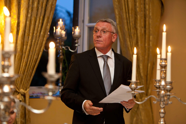 Der Brautvater hält eine Rede. Er steht im Hochzeitssaal zwischen Kerzenständern. Hinter ihm ist ein Fenster geöffnet. Er hält einen weißen Zettel in der Hand.