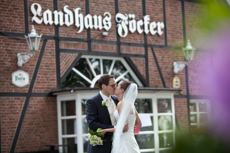 Das Brautpaar küsst sich vor der Location Landhaus.