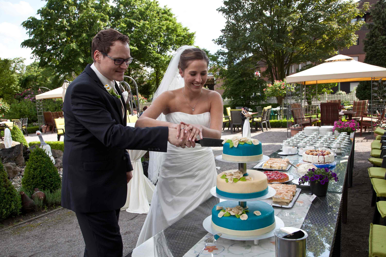 Das Brautpaar schneidet im Garten gemeinsam die Hochzeitstorte an.