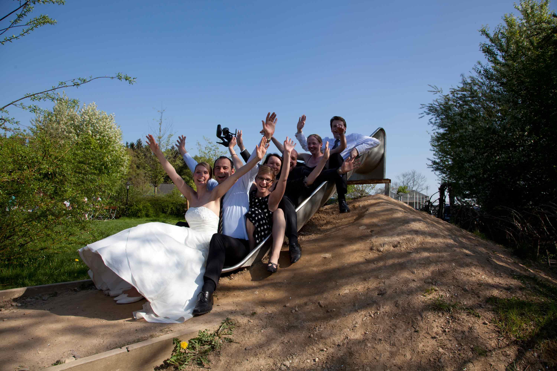 Das Brautpaar sitzt mit den Trauzeugen und den Freunden auf einer Rutsche. Sie heben die Arme in die Luft.
