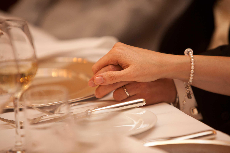 Das Brautpaar hält sich an den Händen während der Feier am Tisch. Detailaufnahme.