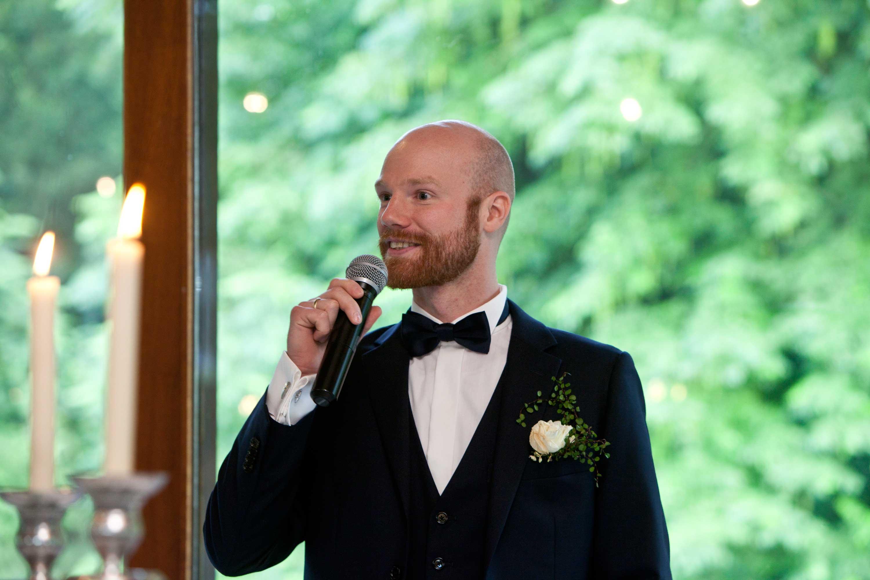 Der Bräutigam hält eine Rede. Er hat ein Mikrofon in der Hand. Er steht vor einem großen Fenster. Vor ihm sind zwei Kerzen.