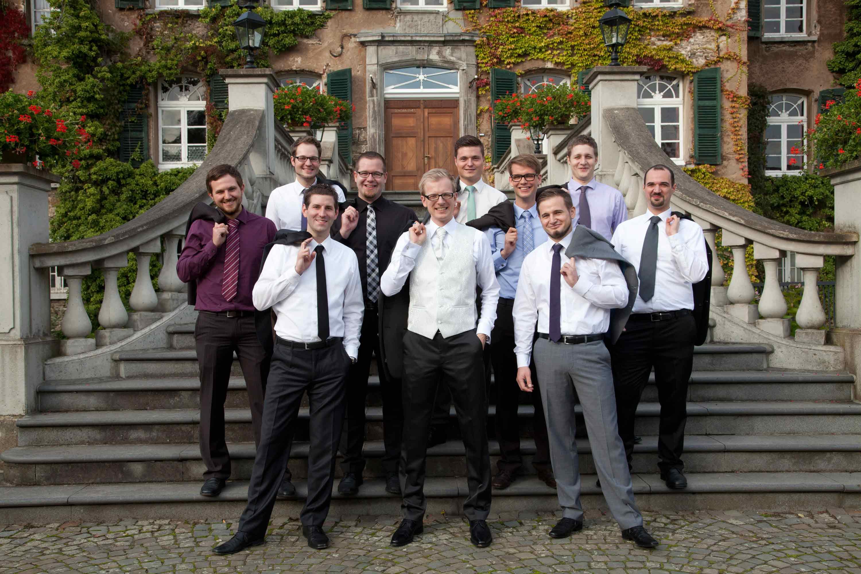Der Bräutigam steht mit seinem Trauzeugen und den Freunden auf einer Treppe. Gruppenfoto. Alle tragen ihre Jackets lässig über der Schulter.