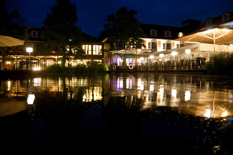 Die Hochzeitslocation bei Nacht. Vor dem Gebäude sind Spiegelungen im Wasser.