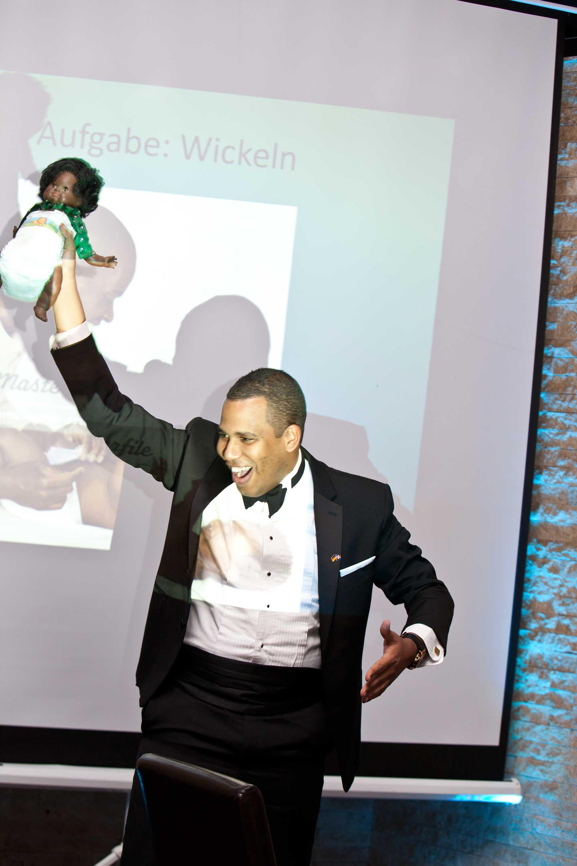 Der Bräutigam hält eine Puppe hoch während eines Hochzeitsspieles. Die Puppe trägt eine Windel. Der Bräutigam steht vor einer großen Leinwand, auf der steht Aufgabe Wickeln.