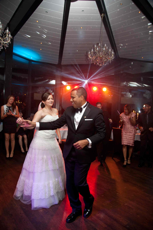 Das Brautpaar beim Tanzen während der Hochzeitsparty. Die Tanzfläche wird mit bunten Lichtern angestrahlt.