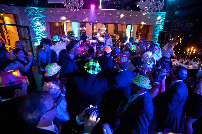 Die Hochzeitsgesellschaft tanzt. Die Tanzfläche ist gefüllt. Die Gäste tragen bunte Hüte.