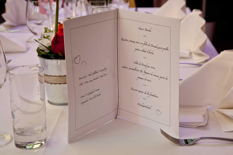 Tischdekoration bei der Hochzeitsfeier. Die Menükarte steht aufgeklappt auf dem Tisch.