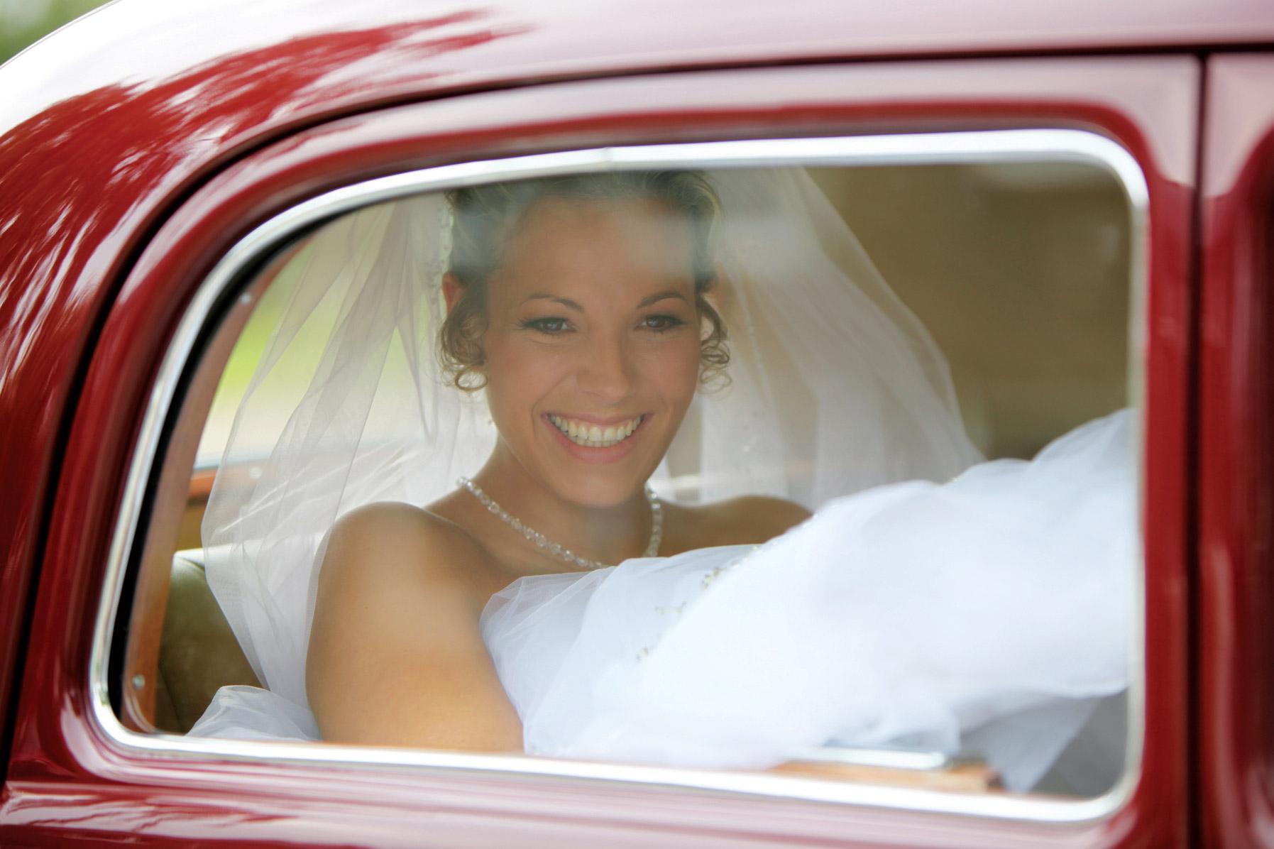 Die Braut sitzt in einem roten Auto. Sie lacht.