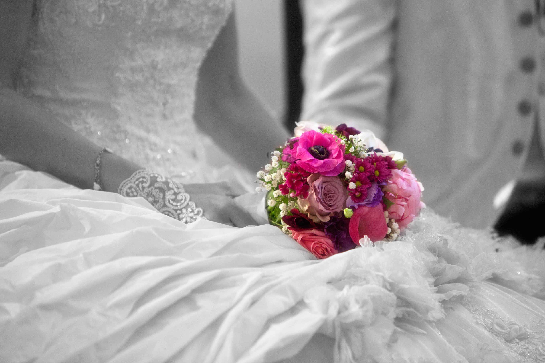 Ein farbiger Brautstrauß liegt auf dem Schoß der Braut. Der Brautstrauß wurde coloriert. Schwarz-weiß-Foto.