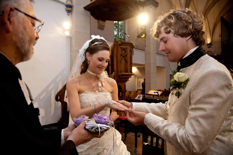 Das Brautpaar ist in einer Kirche. Der Bräutigam steckt den Ring an die Hand der Braut. Der Pfarrer hält das Ringkissen.