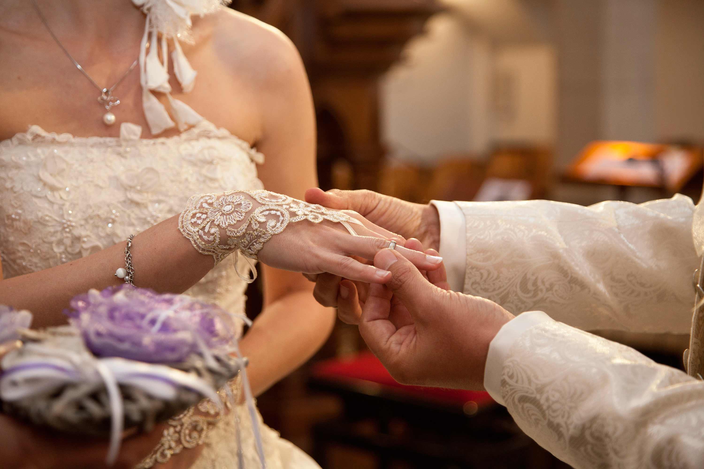 Das Brautpaar ist in einer Kirche. Der Bräutigam steckt den Ring an die Hand der Braut. Die Braut trägt einen Handschuh aus Spitze mit Blumenmotive. Detailfoto.