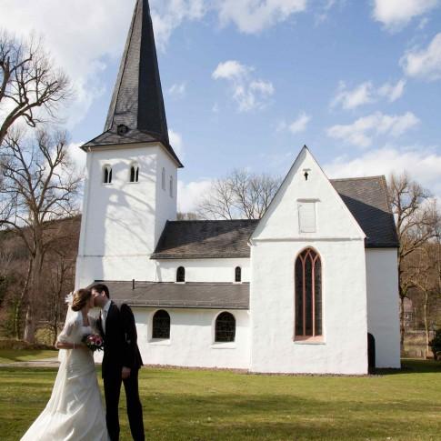 Das Hochzeitspaar küsst sich vor einer kleinen, weißen Kirche.