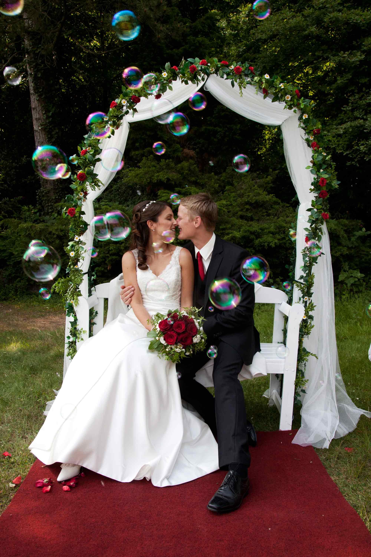 Das Brautpaar sitzt auf einer weißen Bank unter einem Torbogen aus weißem Stoff und roten Rosen. Unter ihnen ist ein roter Teppich. Das Brautpaar ist umgeben von Seifenblasen. Die Braut hält einen Brautstrauß mit roten Rosen in den Händen.