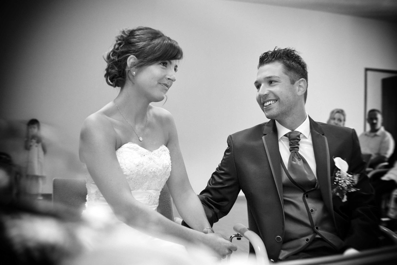 Das Brautpaar während der Trauung. Der Bräutigam schaut die Braut an. Schwarz-weiß-Foto.