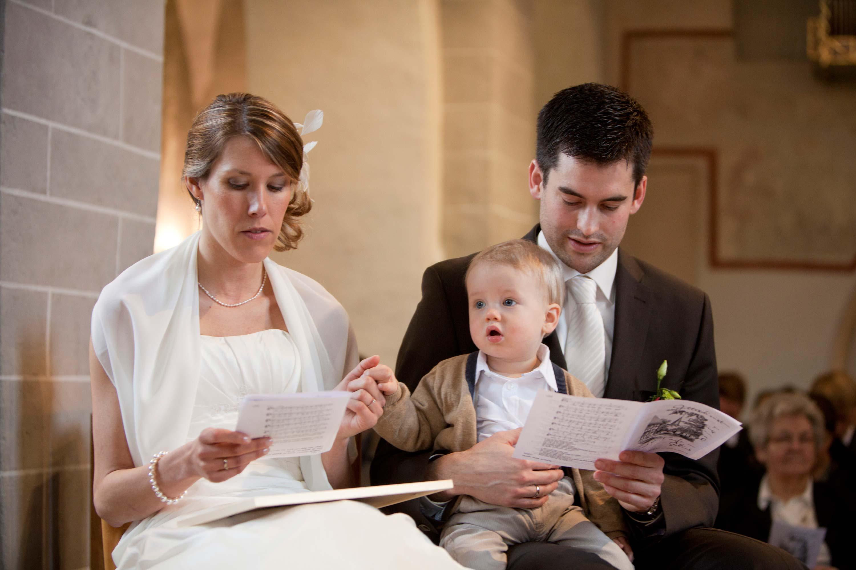 Das Brautpaar während der Trauung mit ihrem Kind. Das Kind hält die Hand der Mutter. Das Kind sitzt auf dem Schoß des Vaters.