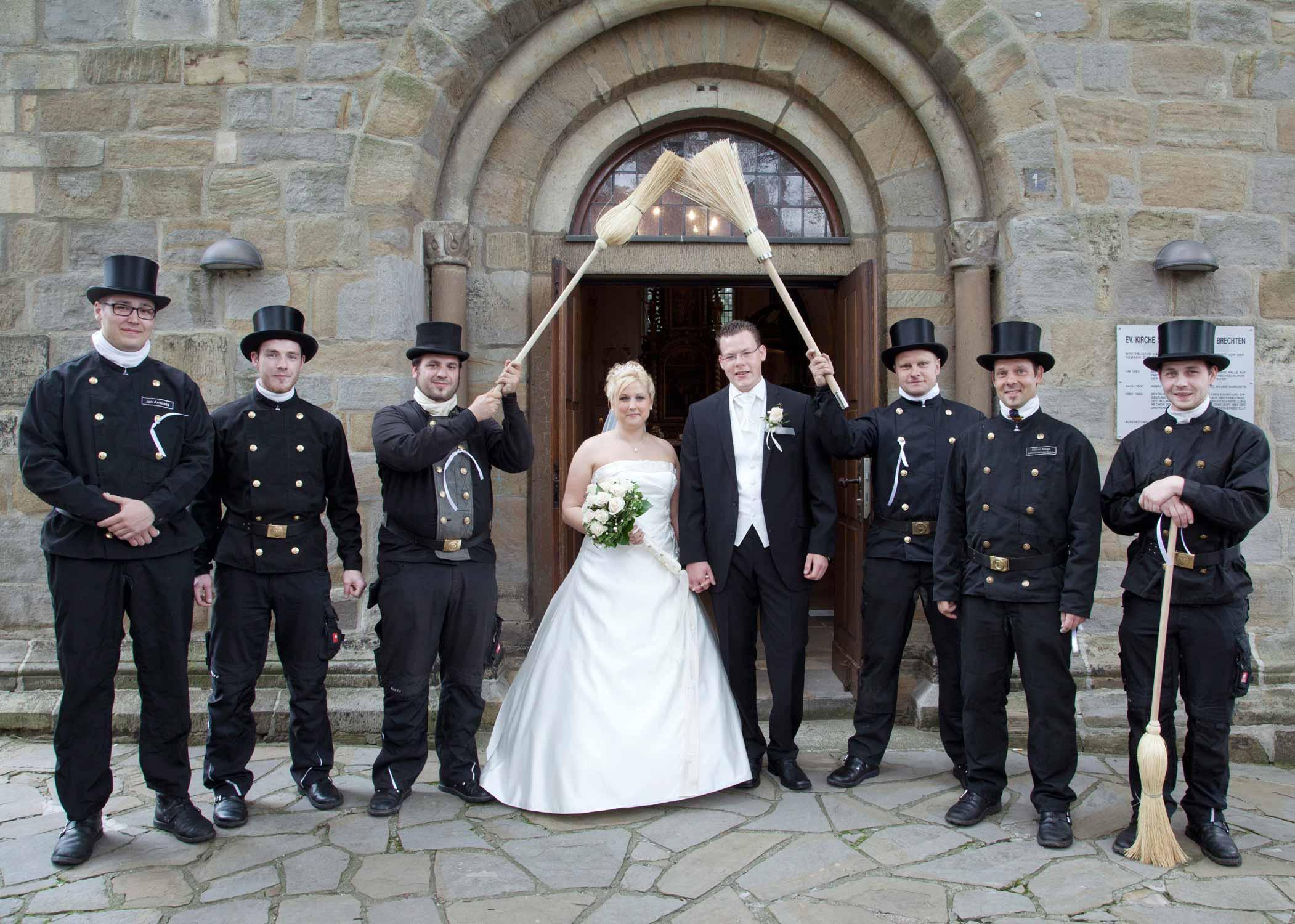Das Brautpaar vor der Kirche mit sechs Schornsteinfegern. Sie halten zwei Besen über das Brautpaar. Die Schornsteinfeger haben schwarze Zylinder auf.